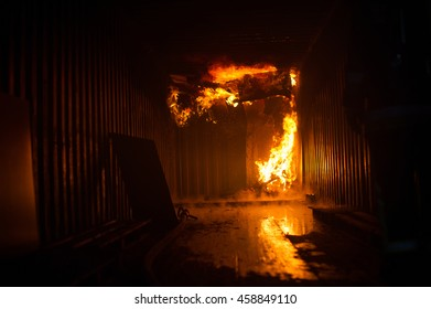 Blazing flames inside a building / container.