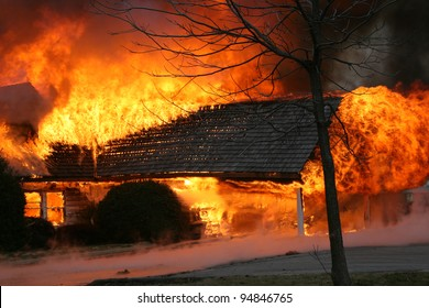 A blazing house fire engulfs a porch.  Fire is one of the most destructive forces of nature, killing thousands each year and leaving nothing but ashes in it's wake
