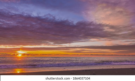 A blazing sunset over the Black Sea. The sun shines through the clouds, painting them orange and scarlet. Waves foaming on the beach. Sunny path on the water and on the sand. Russia