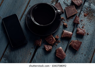 Blcak cup of coffee, mobile phone and pieces of chocolate on a wooden table