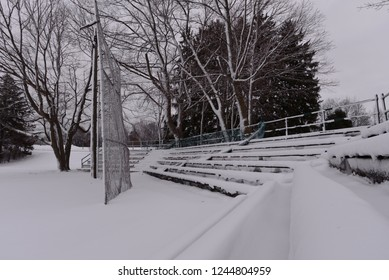 The bleacher sets are coated with heavy snow just after a late fall snowstorm making the field out of use for the rest of the season.