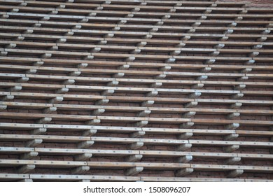 Bleachers in a concert venue. A close-up view of a numbered wooden bleacher benches.