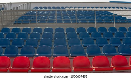 Bleachers in a sports stadium. Red and blue seats in a large street stadium.