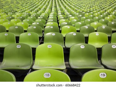 bleachers at stadium, endless rows of green plastic seats