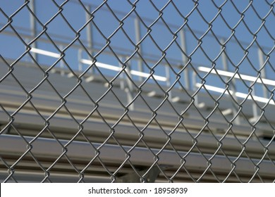 Bleachers in a stadium or school for the fans behind a fence.