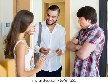 Bleak young couple greeting cheerful young salesman in doorway