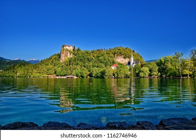Bled Castle surrounded by the Lake Bled, Slovenia. Lake Bled is a lake in the Julian Alps in the region of northwestern Slovenia. It is of mixed glacial and tectonic origin. Popular tourist sight.