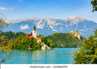 Bled Island with Assumption of Mary church surrounded by the green waters of Lake Bled with castle cliff in the background, Upper Carniola, Slovenia