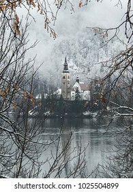 Bled Island on Lake Bled, Slovenia on a cloudy day in the snow