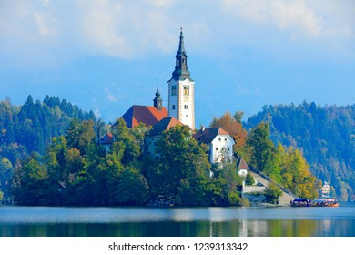 Bled lake island, St Martin Catholic church and Castle. Landscape in Slovenia, nature in Europe.  Foggy Triglav Alps with forest, travel in Slovenia. Beautiful sunrise with blue sky, green nature.