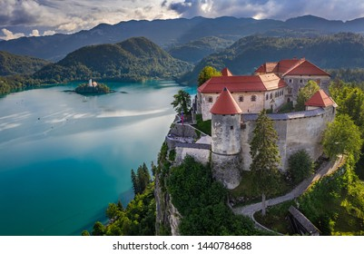 Bled, Slovenia - Aerial view of beautiful Bled Castle (Blejski Grad) with Pilgrimage Church of the Assumption of Maria on a small island and Julian Alps at background at summer time