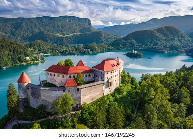 Bled, Slovenia - Aerial view of beautiful Bled Castle (Blejski Grad) with Lake Bled (Blejsko Jezero), the Church of the Assumption of Maria at background on a bright summer day