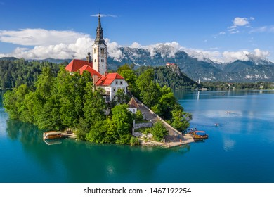Bled, Slovenia - Aerial view of Lake Bled (Blejsko Jezero) with the Pilgrimage Church of the Assumption of Maria, pletna boats, Bled Castle and Julian Alps on a sunny summer day