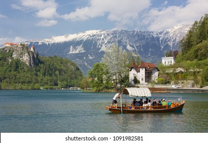 BLED, Slovenia - April 25, 2018: Tourists on a rowboat on lake Bled, with the ancient castle and the snow-capped mountains in the background