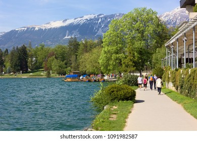 BLED, Slovenia - April 25, 2018: People strolling on the waterfront promenade on Lake Bled, Slovenia, in springtime