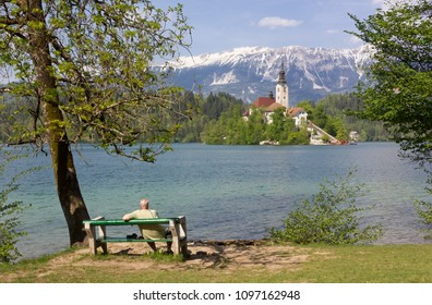 BLED, Slovenia - April 25, 2018: Man sitting on a bench on the shoreline contemplating the church on the Bled island