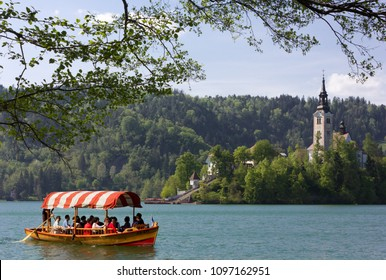 BLED, Slovenia - April 25, 2018: Tourist rowboat on lake Bled, with the island in the background