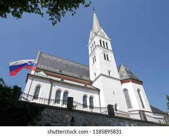 Bled, Slovenia - August 12, 2018: The Church of Saint Martin in Bled, Slovenia. The church with the distinctive roof has been standing on the shores of Lake Bled for centuries and rebuilt in 1905.