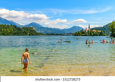 BLED / SLOVENIA - AUGUST 15, 2019: Swimming and bathing in Lake Bled on a background of a beautiful landscape with church on a small island - Slovenia symbol.