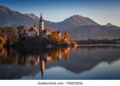 Bled, Slovenia - Beautiful autumn sunrise at Lake Bled with the famous Pilgrimage Church of the Assumption of Maria with Bled Castle and Julian Alps at background