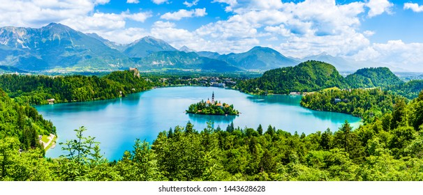 Bled, Slovenia: Beautiful iconic landscape of Lake Bled and the church island in the middle with the castle in the background of white clouded sky seen from Ojstrica viewpoint.