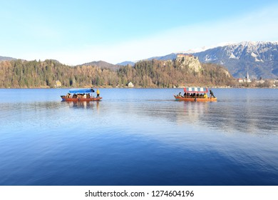 Bled, Slovenia - December 21, 2018:Tourists ride by wooden rowing boats on the Bled Lake.