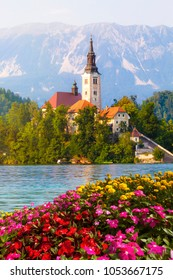 Bled, Slovenia. Island in the middle of the lake with church. Church of St. Martin. Bled is a town on Lake Bled in northwestern Slovenia. Karawanks mountain. Flowers and nature in evidence.