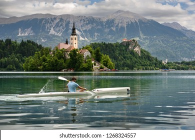 Bled, Slovenia - May 20, 2017: Assumption of Mary pilgrimage church Beld Island and kayaker on Lake Bled with Bled castle on cliff and Sol massive of Karavanke mountains Slovenia