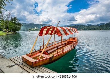 Bled, Slovenia - May 20, 2018: Beautiful Lake Bled in the Julian Alps and old wooden boat. Mountains, clear aquamarine water, tourist boat, lake and dramatic blue sky.