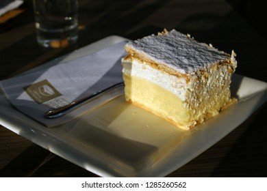 "BLED, SLOVENIJA - JUNE 26, 2018: Traditional slovenian cream cake ""blejska kremna rezina"" illuminated by a low evening sun. The cake has a crisp pastry top and bottom with a thick layer of custard."
