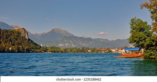 Bled, Upper Carniolan / Slovenia - August 2011: Bled Castle overlooking the lake with a Pletna boat anchored at the shore