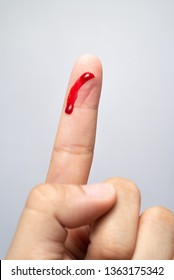 Bleeding blood from the cut finger wound. Injured finger with bleeding open cut wound. Closeup of finger human hand is cut hurt bleeding with bright red blood.