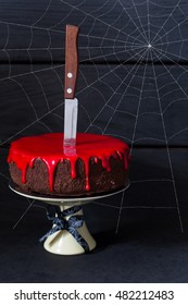 Bleeding monster cake with knife on cake stand and spider web.
