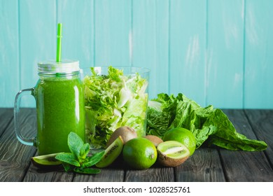 Blended green smoothie with ingredients on wooden table selective focus. Blue background. - Shutterstock ID 1028525761