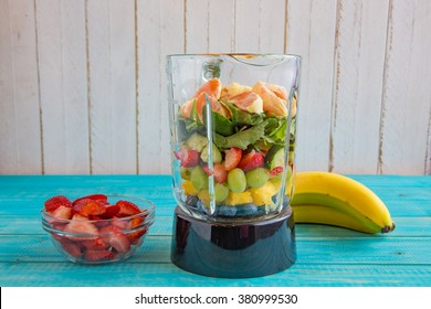 Blender Filled With Organic Fruits and Vegetables Including Oranges, Spinach, Cucumbers, Strawberries, Grapes, Pineapple, and Bananas for a Healthy Smoothie