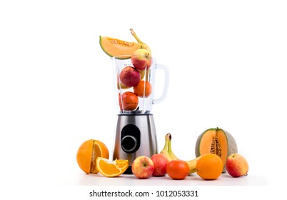 blender with a lot of fruits in front of white background