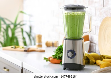 Blender with healthy smoothie and ingredients on table in kitchen