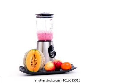 blender with milkshake and a lot of fruits in front of white background