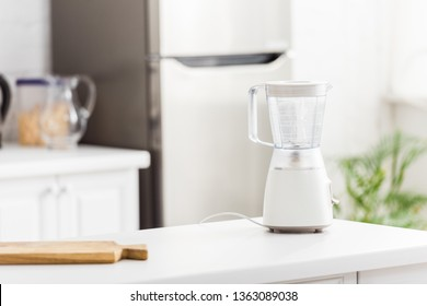 blender near wooden chopping board in modern kitchen