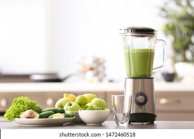 Blender with tasty smoothie and ingredients on table in kitchen