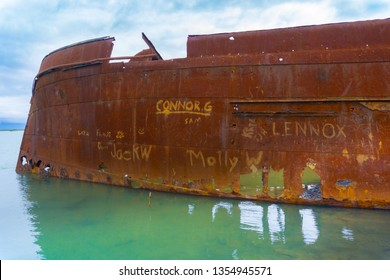 BLENHEIM NEW ZEALAND - OCTOBER 29; Scuttled rusting hulk of old ship Waverley names scratched in rust lying in shallows of Wairau Lagoons on nature walk October 29 2018 Blenheim New Zealand