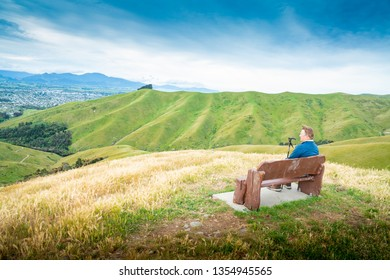 Blenheim New Zealand - October 31;After the climb, seated man taking a break  looking out over scenic Wither Hills landscape green hillside and valley in October 31 2018 Blenheim New Zealand