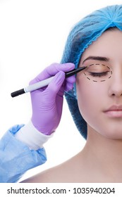 blepharoplasty surgery concept. Doctor drawing marks on female face against white background