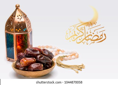 Blessed or generous holy month of Ramadan. Ramadan Kareem or Mubarak Arabic Text, close up of oriental Lantern lamp with dates on wooden plate & rosary on white background. Islamic Greeting Card