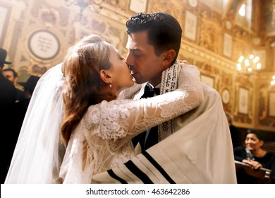 Blessed kiss of Jewish wedding couple standing in the synagogue