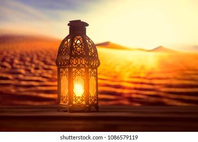 Blessed month of Ramadan. Stock photo. An illuminated Ramadan lamp against a desert background.