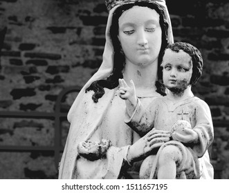 Blessed Virgin Mary holding Baby Jesus in her arms, holding globus cruciger (orb and cross) raising arm in gesture of blessing. Black and white religious photography in France
