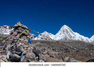 Blessing prayer flags with snow rocky mountains under a clear blue sky during the hike from Lobuche to Gorak Shep, Everest base camp trekking trail, EBC, Sagarmatha National Park, Nepal