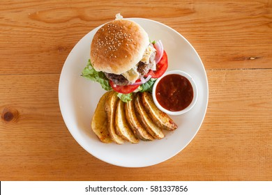 A Bleu (Blue) cheese hamburger with fries and barbecue sauce from above on a wood tabletop