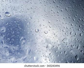 bleu sky behind rain drops on a window